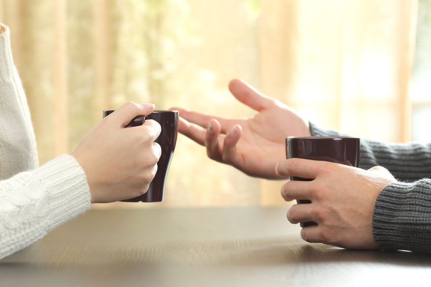 65879359 - back light profile of hands of 2 friends or couple talking holding coffee cups sitting in a table at home with a window in the background