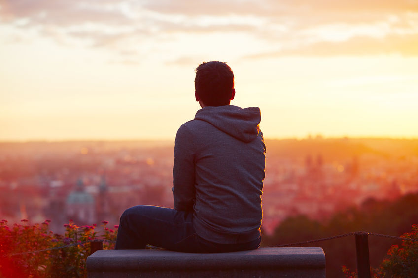 45779081 - young man is looking at the sunrise.